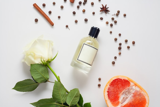 アロマオイルはシナモンと白いバラとグレープフルーツ、白い壁にあるスパイスで飾られています。香水、ボディケア、アロマオイルの成分の成分のコンセプト。