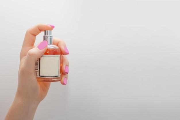 Рука, держащая бутылку, держит указательный палец на распылителе на белой стене. концепция парфюмерии или ухода за женщинами.