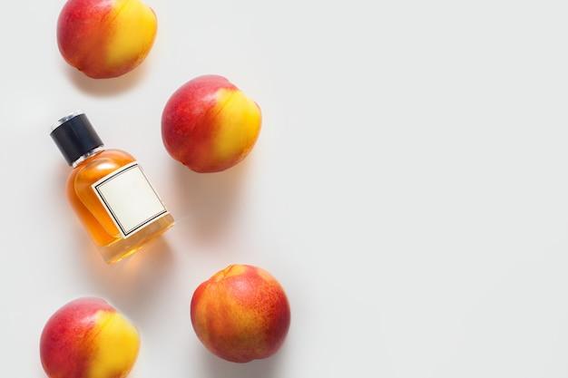 Бутылка персикового масла, украшенная персиками на белой стене, слева от места для текста, с копией пространства. концепция ароматического масла, ингредиентов ароматического масла или ароматерапии.