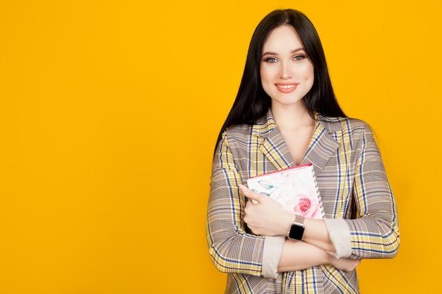 明るい黄色の壁にビジネススーツを着た、笑顔と手にノートを持った女性。教育、学生またはビジネスの女性の概念。