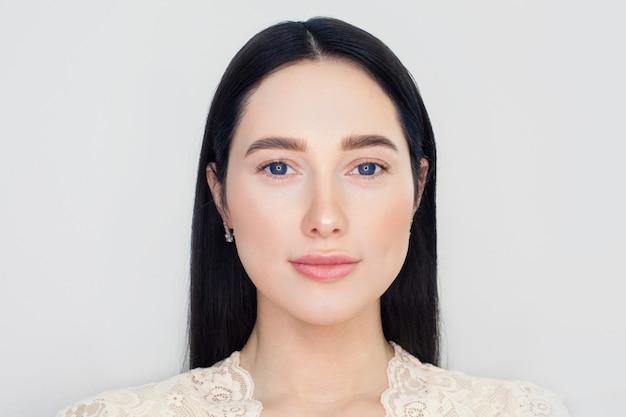 白い壁に透明肌の女性の顔。肌のクレンジング、クリームを持ち上げる効果、顔の美しさと若さの概念。