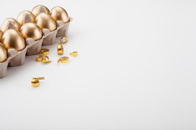 Золотые яйца в кассете, крупным планом, на белом фоне. концепция пасхи.
