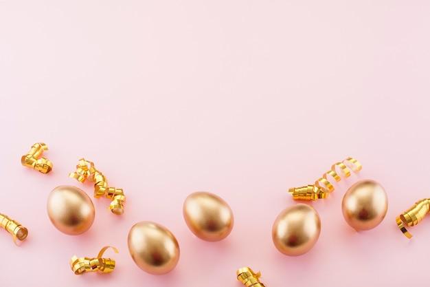 コピースペースのある黄金の卵とピンクの背景。イースターのコンセプト。