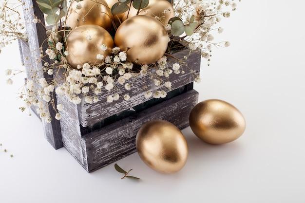 Золотые яйца с весенними цветами. концепция пасхи.