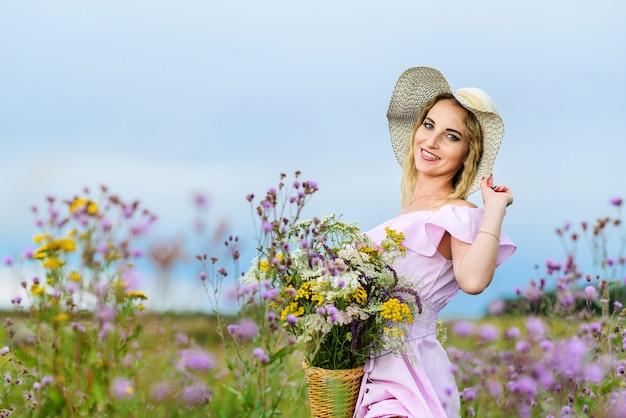 花束と麦わら帽子の笑顔の女の子がフィールドに立っています。国の休暇の概念。