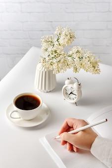 女性の手は、一杯のホットコーヒーとライラックの花瓶の横にある白いテーブルに横になっているノートに鉛筆で書いています。