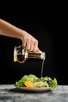 Женская рука наливает свежеприготовленный салат из стеклянной бутылки с оливковым маслом.