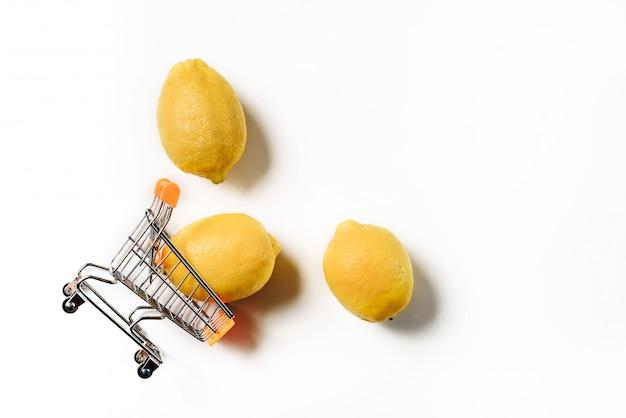 Перевернутая корзина супермаркета с тремя лимонами