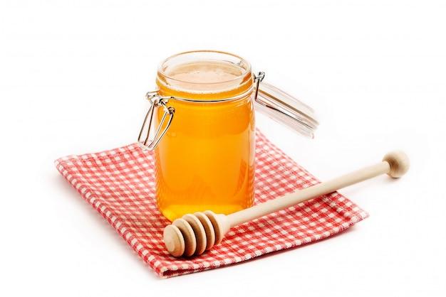 蜂蜜と分離された市松模様のナプキンに木の棒が付いているガラス瓶