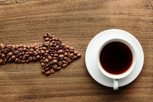 Кофейные зерна в форме стрелки указывают на чашку кофе.