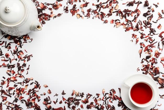 Пищевая рамка из отливок из гибискуса, чайника и чашки с чаем, изолированных на белой стене