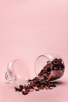 ひっくり返されたガラスの瓶と散在するハイビスカス茶の花びら