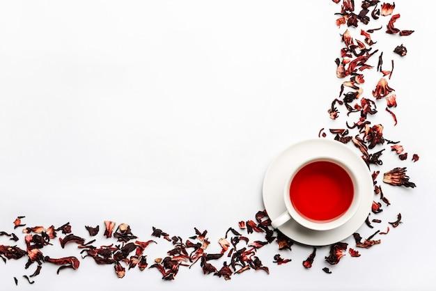 Рамка еды с чашкой и лепесток чая гибискуса изолированные на белой стене с космосом для текста.
