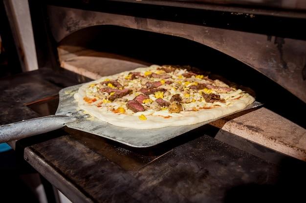 Процесс приготовления пиццы. шеф-повар пекарь ставит сырую пиццу в духовку. кухня.