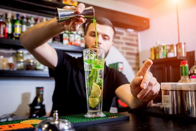 Бармен делает безалкогольный коктейль в баре. свежие коктейли бармен за работой. ресторан. ночная жизнь.