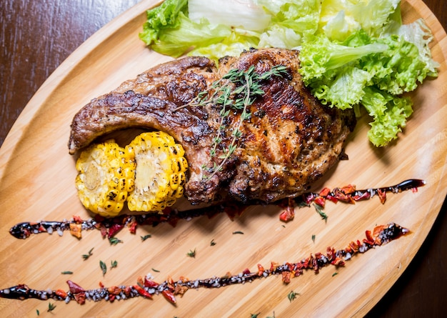 豚肉のグリルリブ、トウモロコシと木の板にサラダ。スパイシーなアメリカンフード。レストラン。