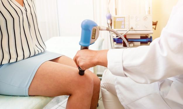 Ударно-волновая терапия. магнитное поле, реабилитация. врач физиотерапевт выполняет операцию на колене пациента