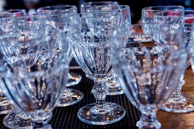 レストランのバーラックの上の棚のワインとマティーニのグラス。空のきれいなグラスのバー。