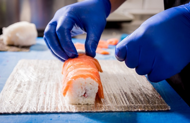 Процесс приготовления суши и роллов на кухне ресторана. повара руки с ножом.