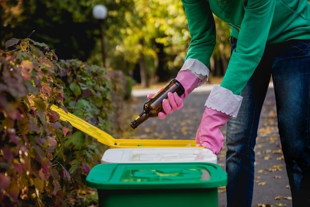 ボランティアの女性が公園の通りでゴミを分別します。リサイクルの概念。廃棄物ゼロのコンセプト。自然