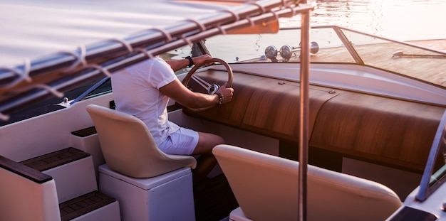 セーリングヨットの若い男。ハンドルを握る手