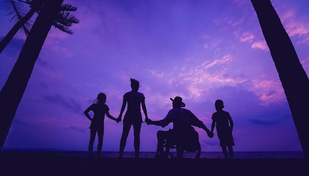 ビーチで家族と一緒に車椅子の障害者の男性。夕暮れ時のシルエット