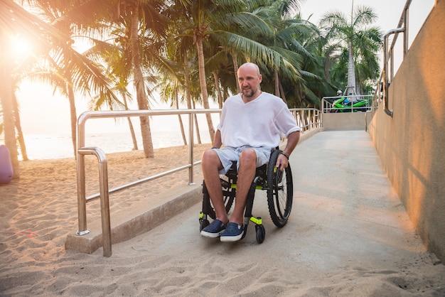 車椅子の障害者が傾斜路をビーチに移動します。