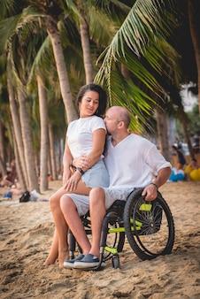 ビーチで妻と車椅子の障害者の男性。