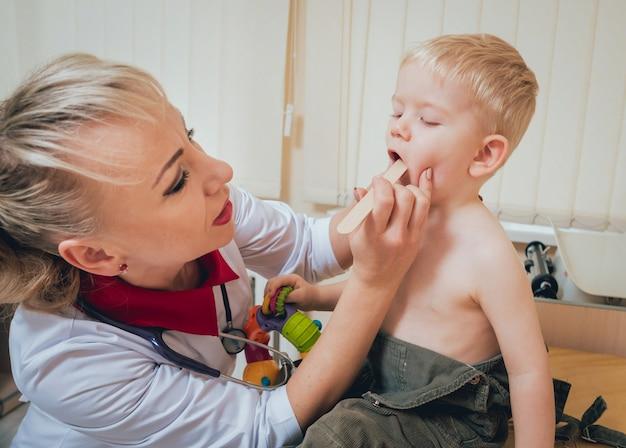 Педиатр осматривает новорожденного ребенка с помощью шпателя