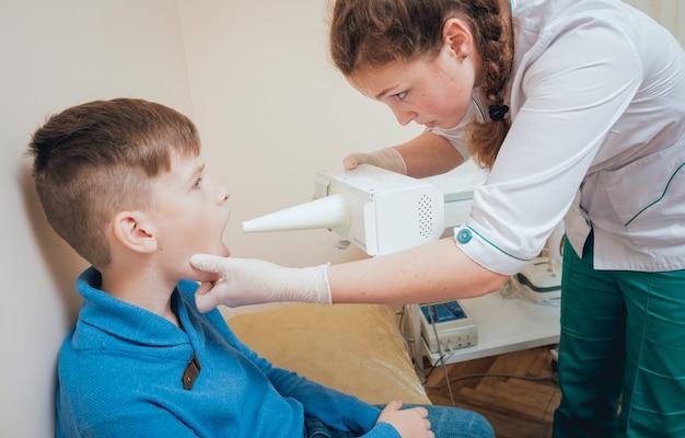 若い男の子の喉頭の治療とウォーミングアップ。現代の小児科。