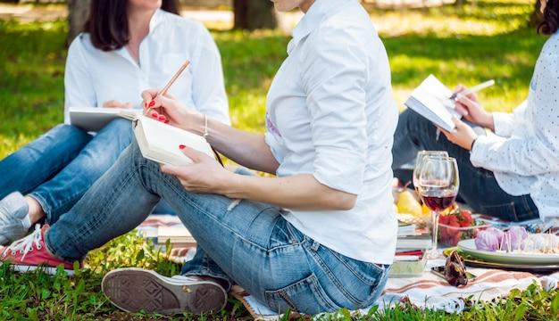 スケッチブックで絵を描く美しい少女。公園で