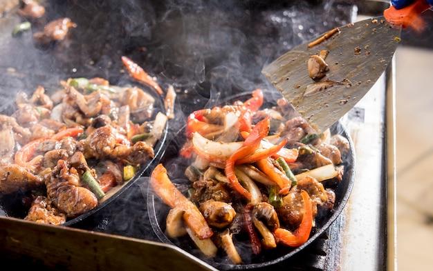 ニンジン、タマネギ、キノコのビーフシチューをワインソースで調理するシェフ。