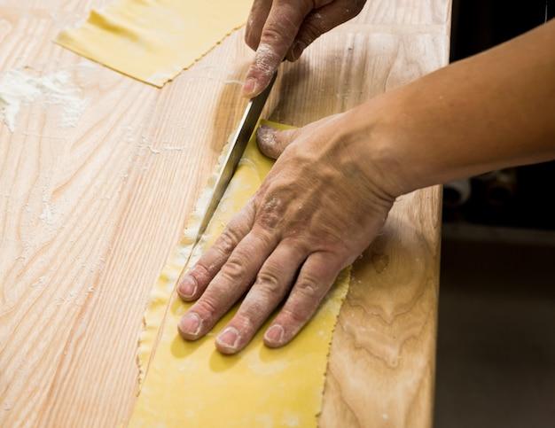 Шеф-повар раскатывает тесто с помощью макаронной машины. машина для производства макаронных изделий.