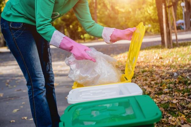ボランティアの女の子が公園の通りでゴミを分類します。リサイクルの概念。
