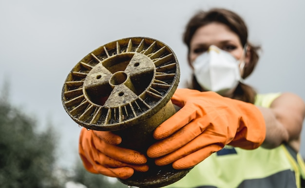 Женщина-волонтер помогает очистить поле от ядерных отходов и пластикового мусора.