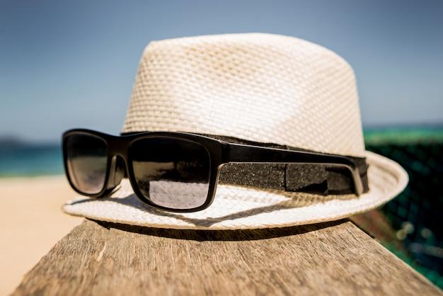 Шляпа и солнцезащитные очки на море.