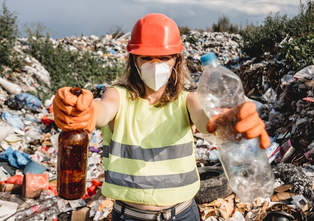 Женщина-волонтер помогает очистить поле от пластикового мусора.