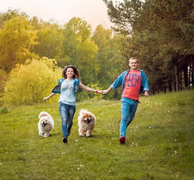 Молодая пара с собаками в парке