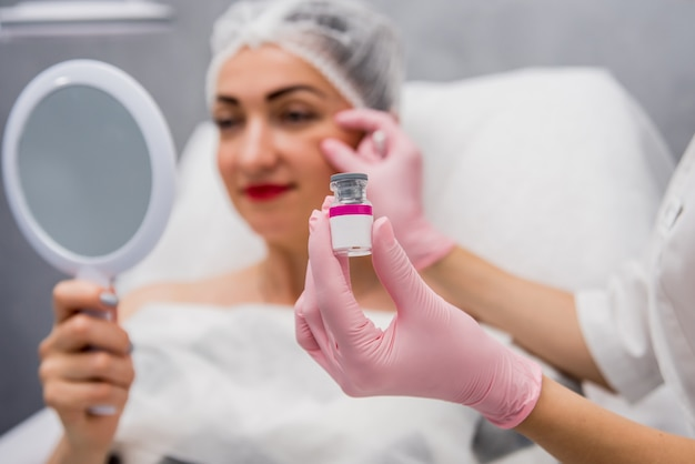 Врач косметолог проводит процедуру инъекций лица.