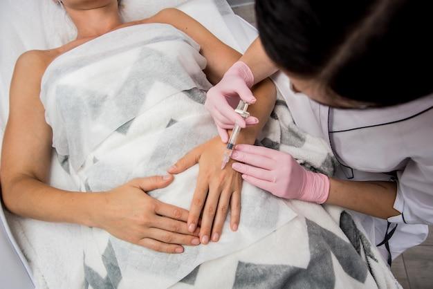Врач косметолог проводит процедуру уколов рук.