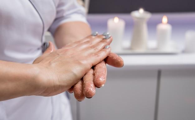 Массажистка наносит на руки ароматическое масло, готовится к массажу в спа-центре