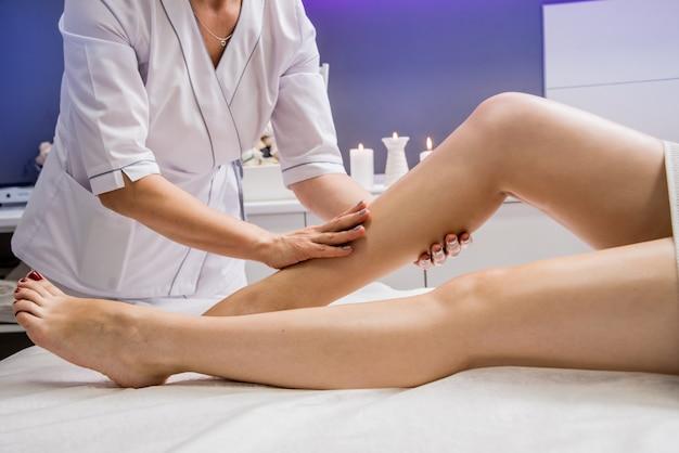 スパサロンでオイルで足マッサージを楽しむ若い女性。美容学