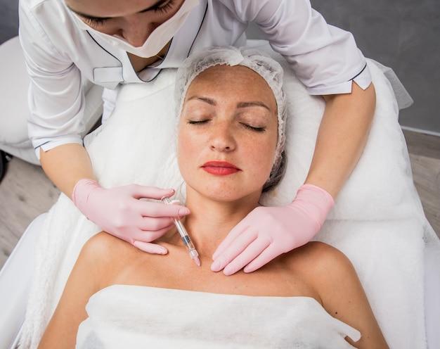医師美容師がネックライン注射の手順を行います。ビューティーサロンで若い女性。