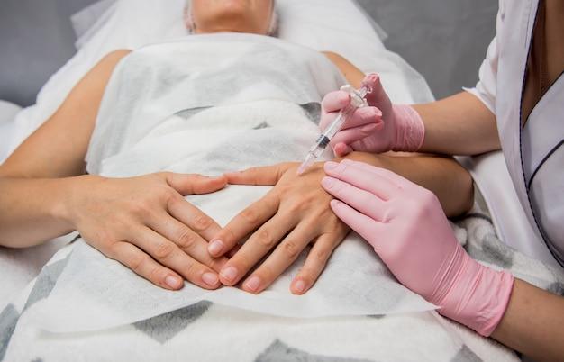 医師美容師が腕の注射の手順を行います。ビューティーサロンで若い女性。