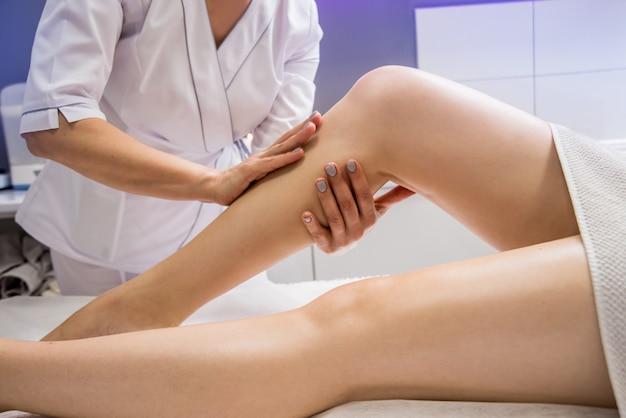 スパサロンでオイルで足マッサージを楽しむ美しい若い女性。美容学