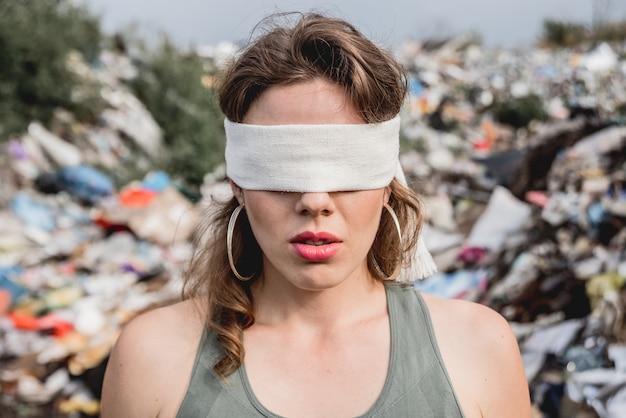 Женщина-волонтер с завязанными глазами на свалке из пластикового мусора. день земли и экология.