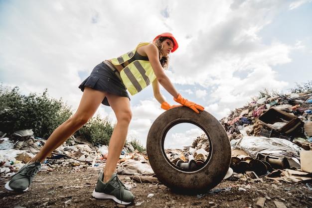 Женщина-волонтер помогает очистить поле от пластикового мусора и старых шин. день земли и экология.