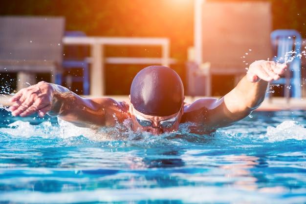 スイミングプールで泳いでいる若い運動男