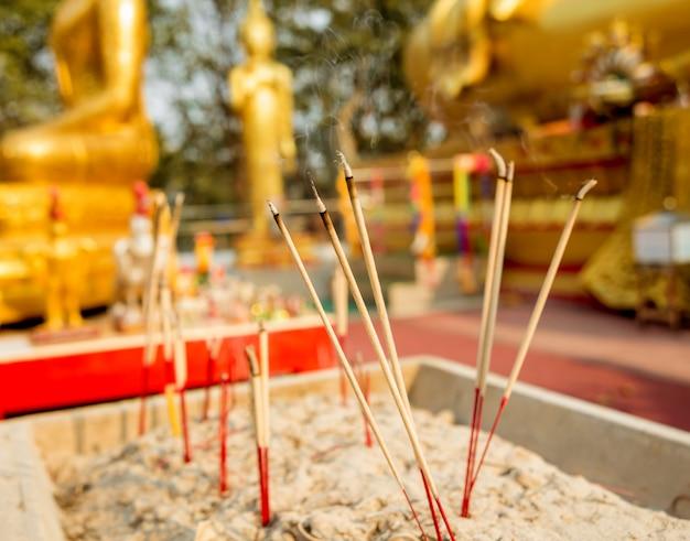 Символы буддизма. горящие ароматические палочки. юго-восточная азия. детали буддийского виска в таиланде.