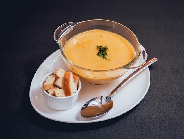 暗い背景にクリームとパセリとカボチャとニンジンのスープ。